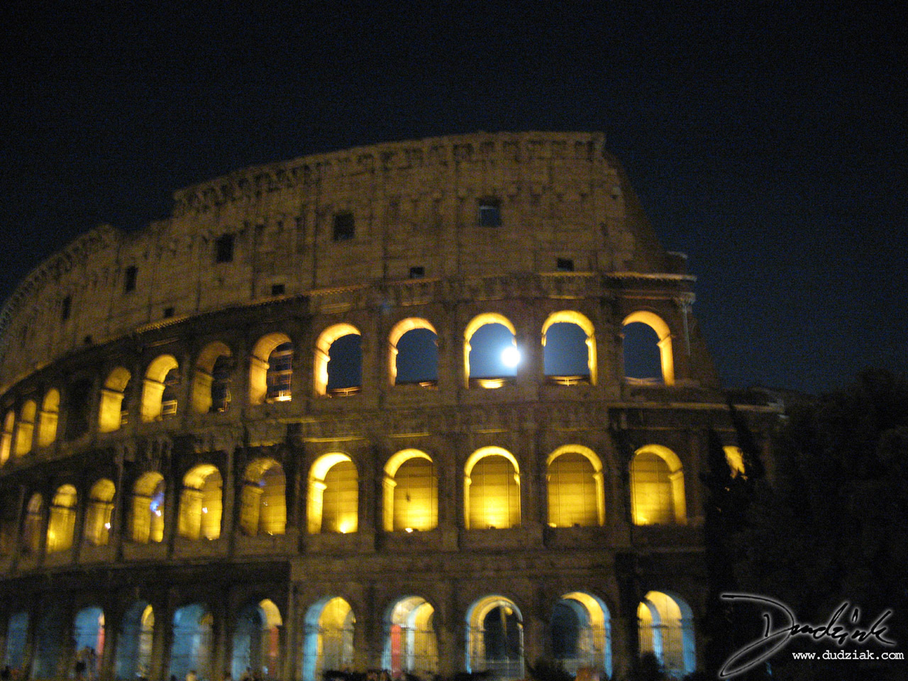 Picture of the Roman Colosseum at night with the moon shining through an arch.  Rome, Italy.
