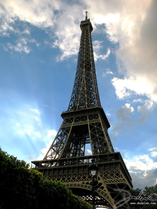 Picture of the Eiffel Tower in Paris, taken while lying in the grass on the Champ de Mars during a break in the clouds.  The sun coming through behiend the Eiffel Tower is quite nice.