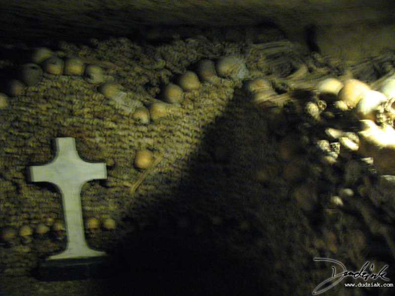 Human skulls with a cross in the Paris Catacombs