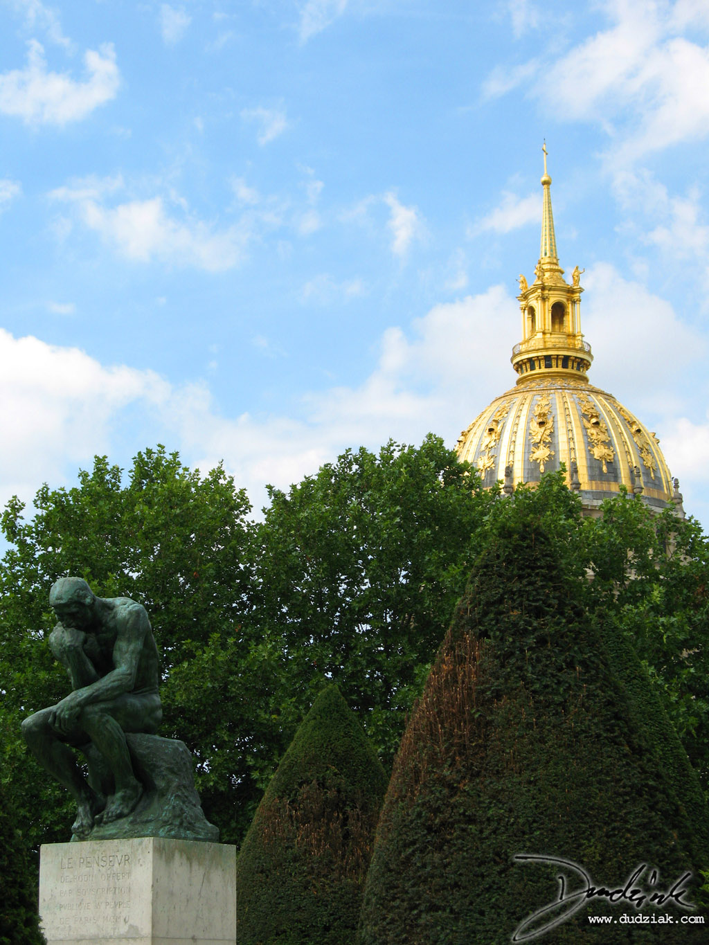 "Picture of ""The Thinker"" (le Penseur) sculpture by Rodin in the Rodin Museum (Musee Rodin) in Paris with the dome of Les Invalides in the background."