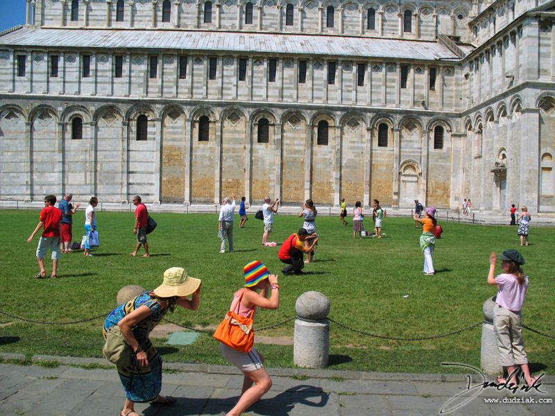 People on the Campo dei Miracoli (field of miracles) posing to get their pictures taken with the leaning tower of Pisa.