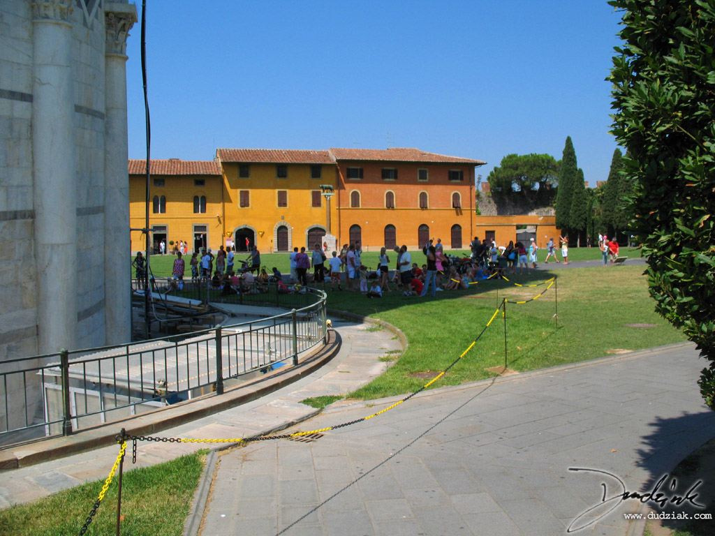 People hanging out in the shadow of the Leaning Tower of Pisa.
