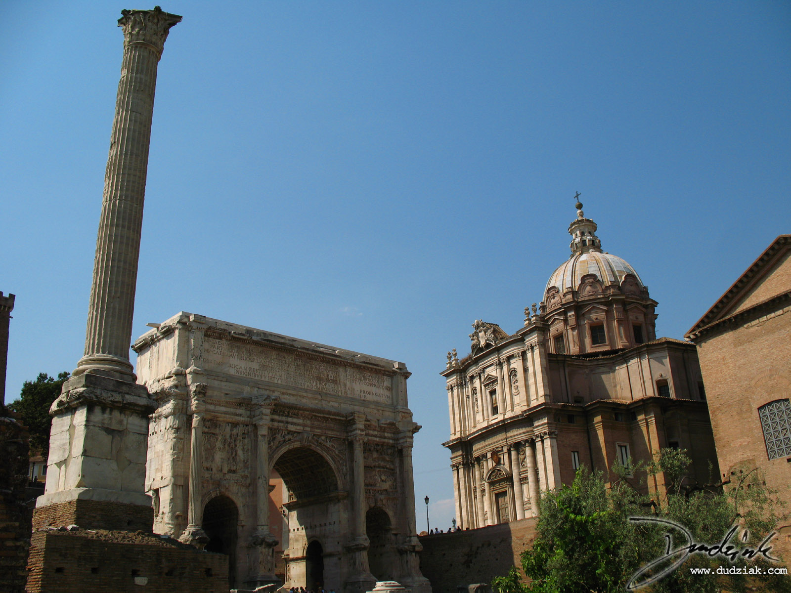 Picture of the Arch of Septimius Severus standing in the western side of the Roman Forum with the Column of Phocas in the foreground.