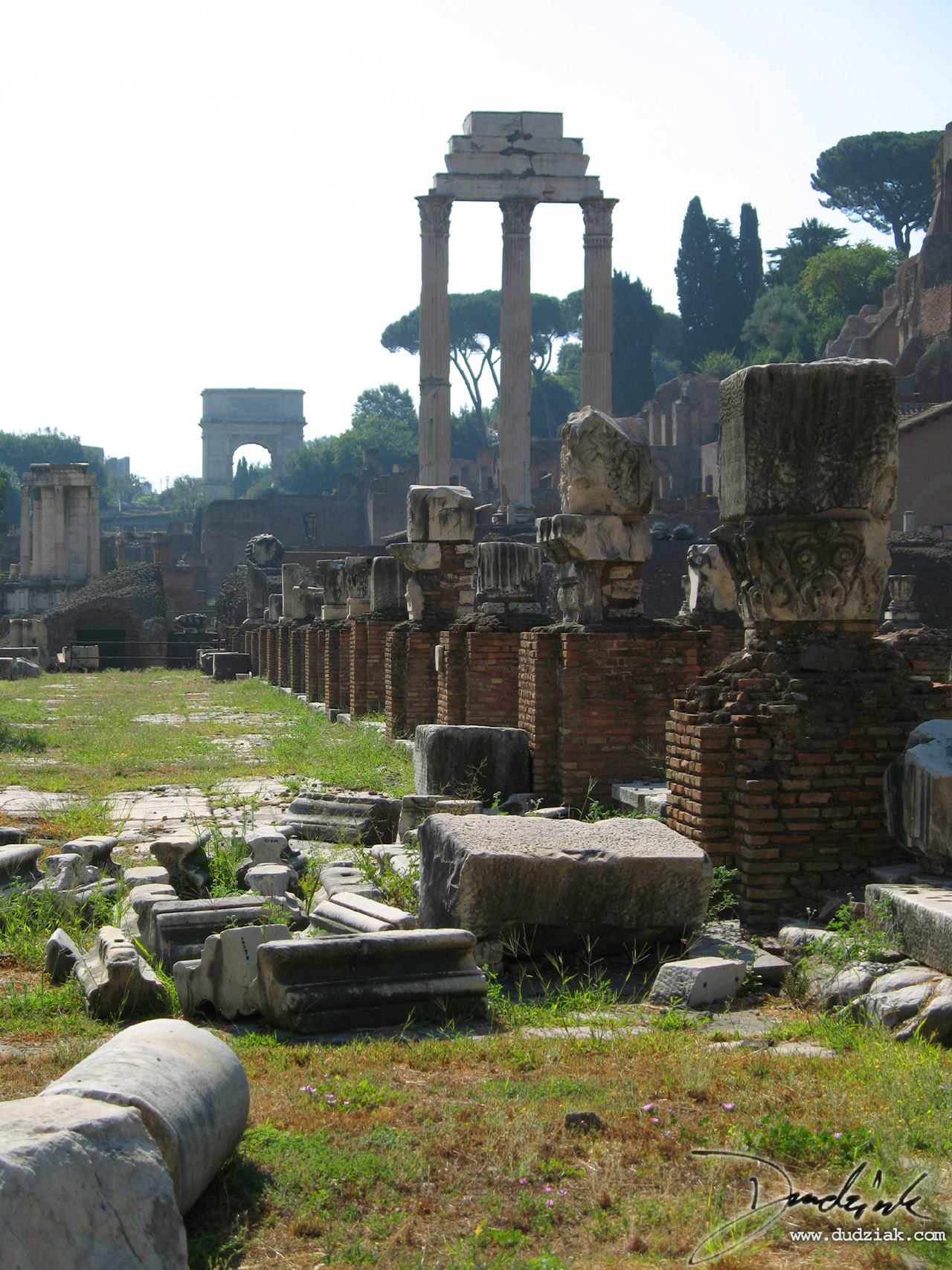 The three Remaining columns of the Temple of Castor and Pollux in the Roman Forum in Rome, Italy.  The Arch of Titus can be seen clearly in the distance.