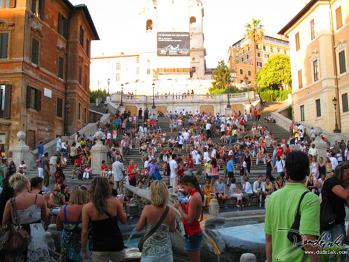 Picture of the Spanish Steps (Scalinata della Trinità dei Monti) with a crowd of people sitting in the shade in Rome, Italy.
