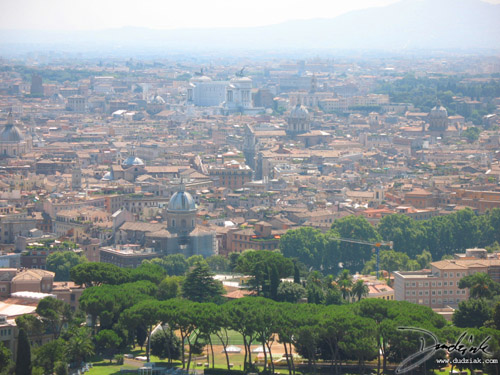 Picture of the city of Rome as seen from the balcony of Saint Peter's Basilica dome.  The colosseum can be seen in the distance.