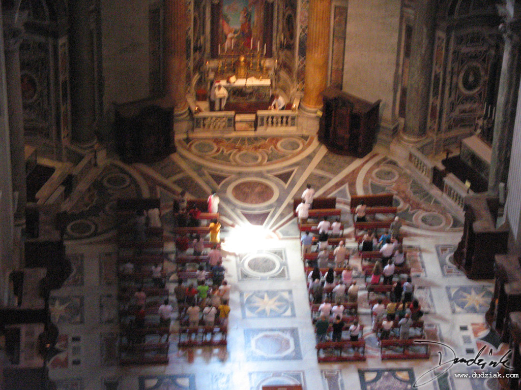 View of a church service in a section of Saint Peter's Basilica.  Picture taken from interior dome balcony.
