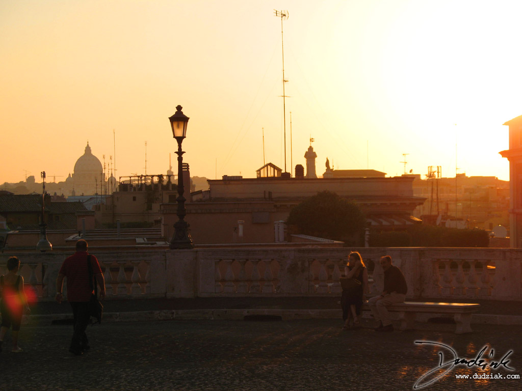 Picture of the Roman skyline at sunset with Saint Peter's Basilica dome in the distance.