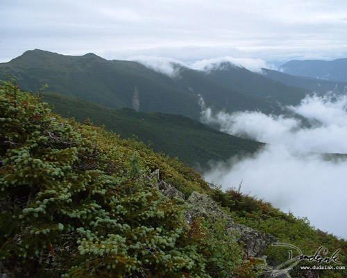Picture from Mt. Washington with clouds rolling over nearby mountains.
